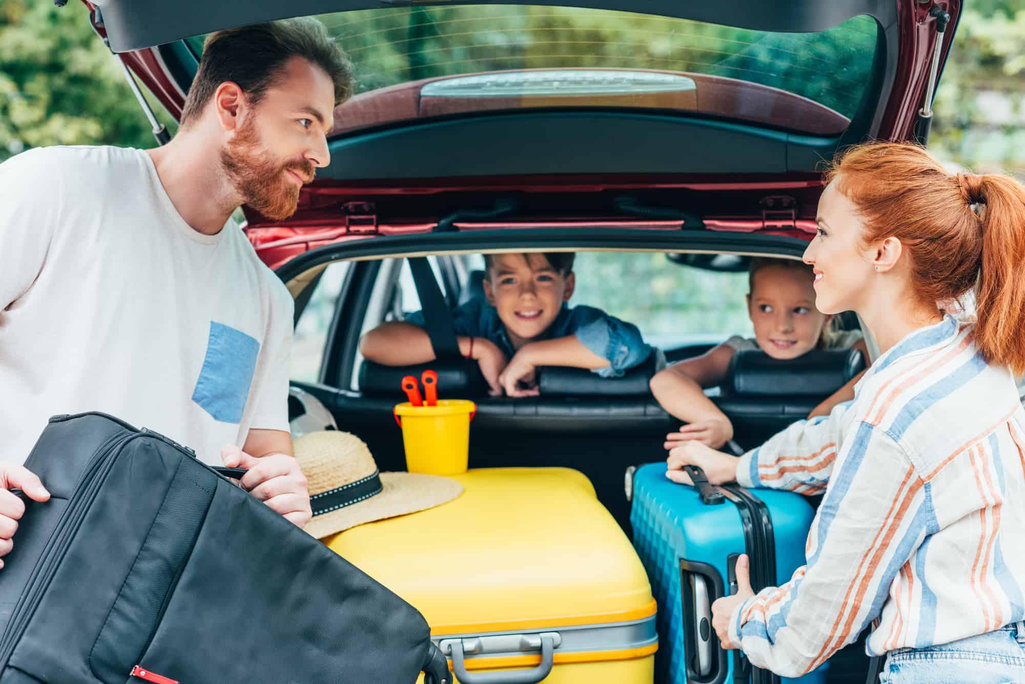 familie med to børn er ved at pakke bilen med kufferter på vej på bilferie ferie