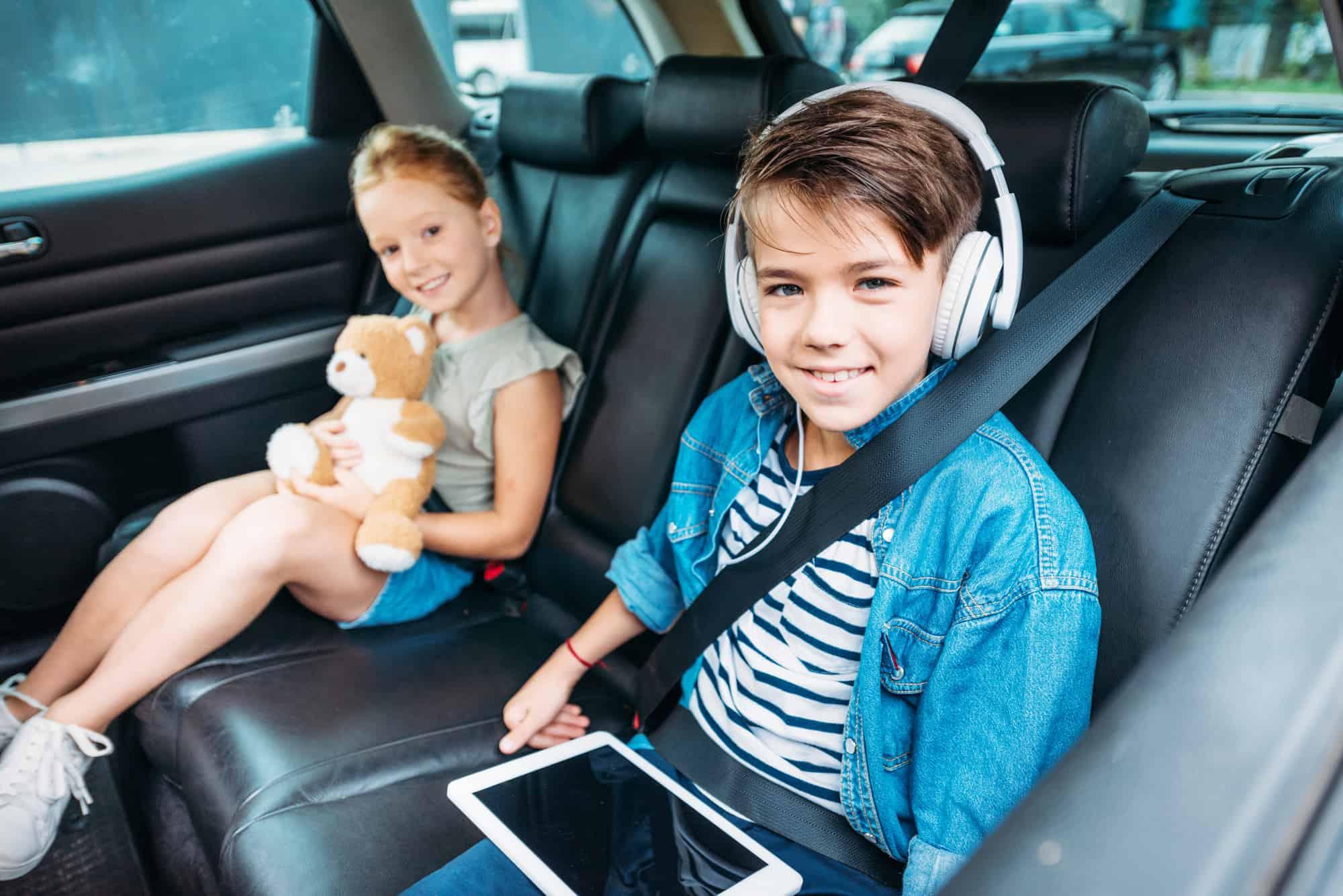 to børn på bagsædet i en bil pigen med en bamse og drengen med en ipad ferie