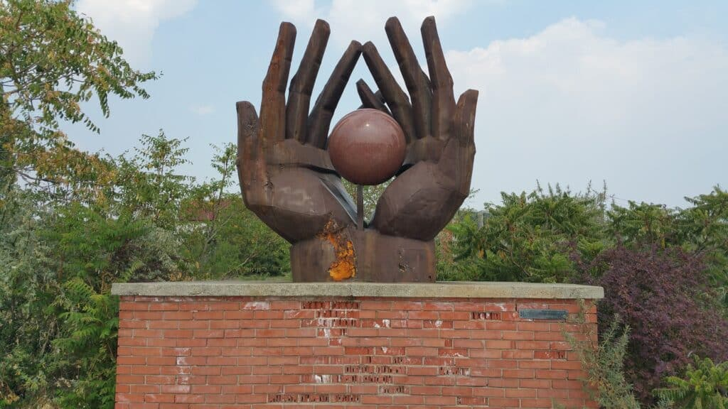billede af hænder fra memento park med kommunistiske symboler og helteskikkelser budapest